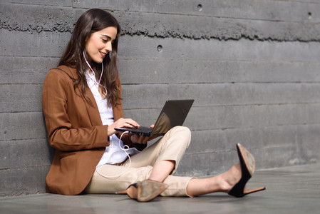 Young businesswoman sitting on floor looking at her laptop compu