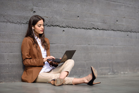 Young businesswoman sitting on floor looking at her laptop computer