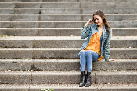 Woman with nice hair wearing casual clothes in urban steps