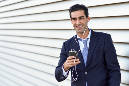 Businessman wearing blue suit and tie using a smartphone