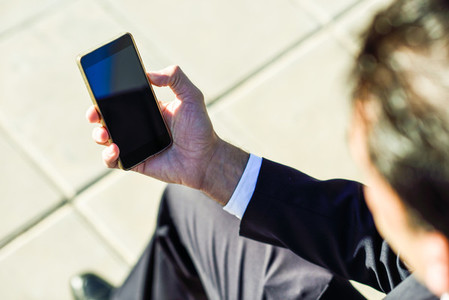 Businessman using his smartphone in the street