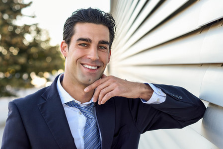 Young businessman wearing blue suit and tie in urban background