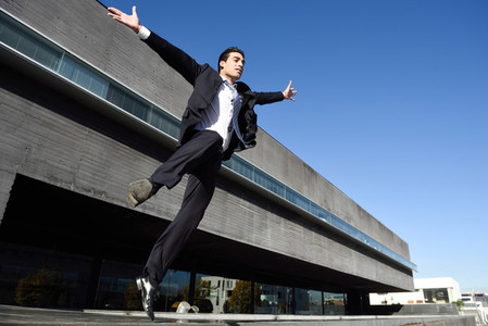 Businessman wearing blue suit and tie jumping in urban backgroun