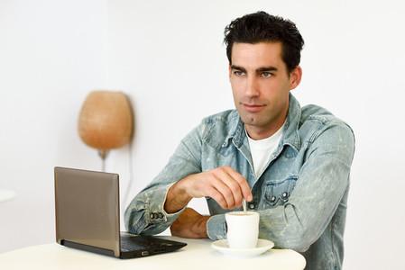 Good looking man wearing denim shirt sitting in a coffee bar