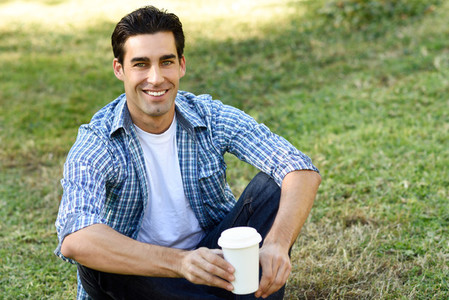 Man drinking coffee to go in an urban park