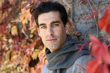 Handsome man wearing winter clothes in autumn leaves background