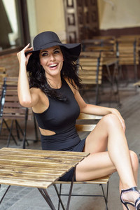 Woman wearing black seductive dress sitting in a outdoors bar