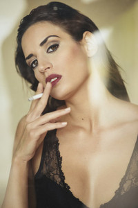 Young beautiful brunette woman in lingerie smoking cigarette