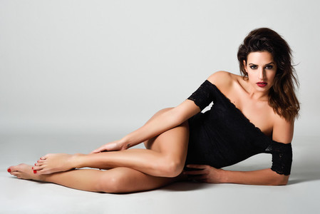 Young brunette woman in black lingerie lying on the floor