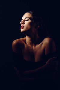 Young brunette woman in black lingerie in chiaroscuro lighting