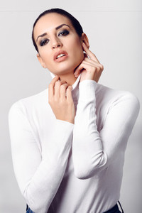 Young brunette woman wearing white poloneck in studio shot