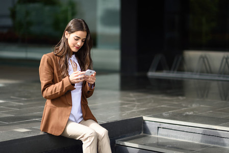 Businesswoman texting with a smartphone next to an office buildi