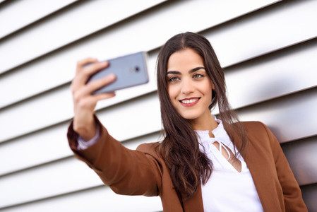 Young woman taking selfie photograph with smartphone in urban ba