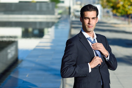 Young handsome businessman adjusting a tie in urban background