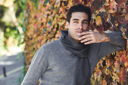 Handsome man wearing winter clothes in wooden background