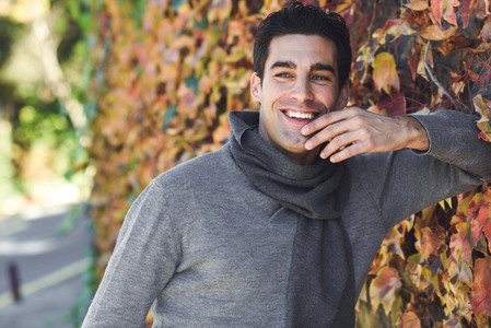 Man wearing winter clothes smiling in autumn leaves background
