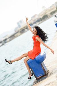 Brunette woman wearing orange short dress in a harbor