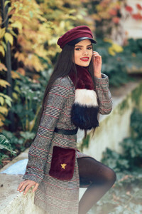 Young girl with very long hair smiling and wearing winter coat and cap in autumn leaves background