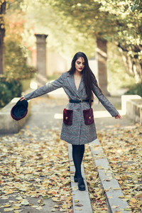 Young girl with very long hair wearing winter coat and cap in urban park full of autumn leaves