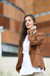 Young woman with nice hair standing outside of office building