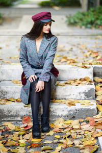 Young beautiful girl wearing winter coat and cap sitting on steps full of autumn leaves