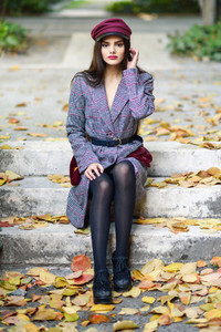 Young beautiful woman wearing winter coat and cap sitting on steps full of autumn leaves
