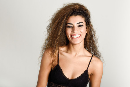 Young happy woman with curly hairstyle smiling
