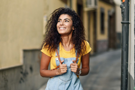 Young North African woman with black curly hairstyle outdoors