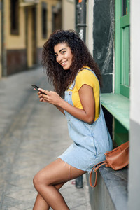 African woman sitting outdoors texting with her smart phone