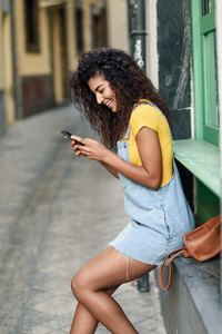 Young North African woman texting with her smart phone outdoors