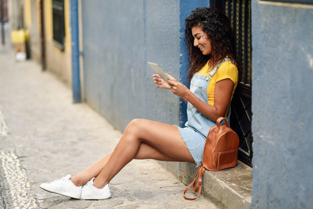 Young Arab woman looking at her digital tablet outdoors