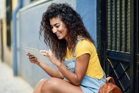 Young Arab woman using her digital tablet outdoors