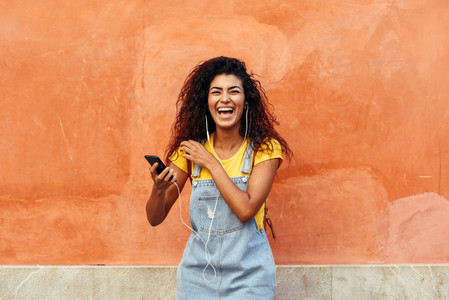 Black woman laughing and listening to music with earphones
