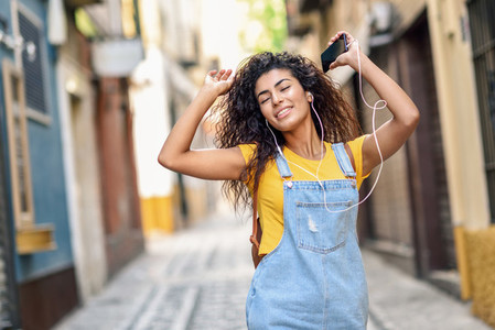 Attractive African girl listening to music with earphones outdoors