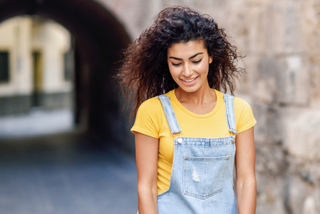 Young Arab woman with curly hairstyle outdoors