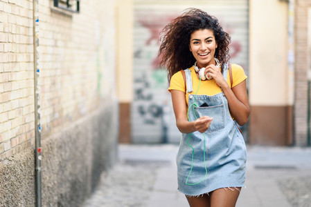 Young African woman with headphones walking outdoors