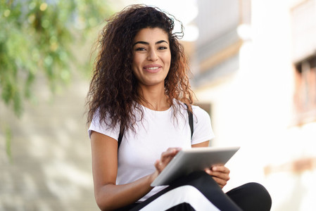 Smiling African woman using digital tablet outdoors