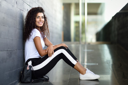 Happy African woman with black curly hairstyle sitting on urban