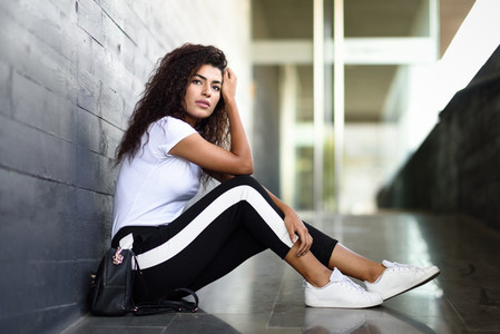 African woman with black curly hairstyle sitting on urban floor