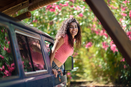 Happy Arab girl peeking out the window of a van