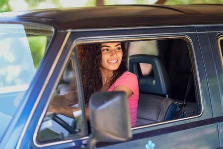 Young Arab woman driving an old van in nature