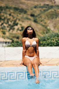 Relaxed woman sunbathing on the edge of a swimming pool