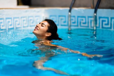 Beautiful tanned woman in bikini relaxing in swimming pool