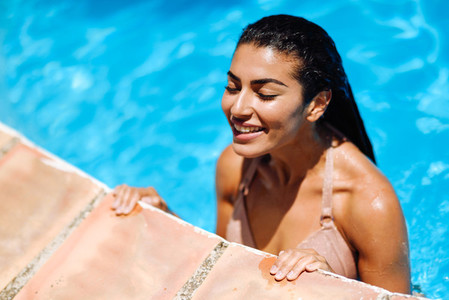 Beautiful Arab woman relaxing in swimming pool