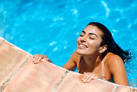 Beautiful Arab woman relaxing in swimming pool