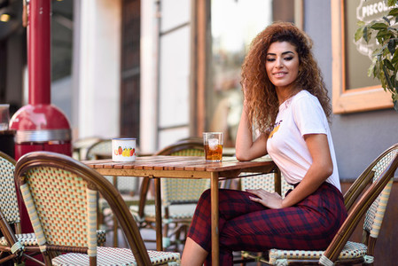 Arab girl in casual clothes drinking a soda in an outdoors bar