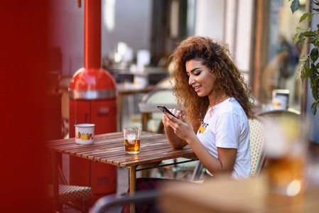 Arab woman in an urban bar at her smartphone