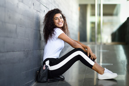 Happy African woman with black curly hairstyle sitting on urban floor