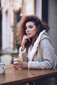 Arab girl in casual clothes drinking a soda outdoors