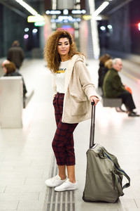 Young arabic female tourist waiting her train in a subway statio